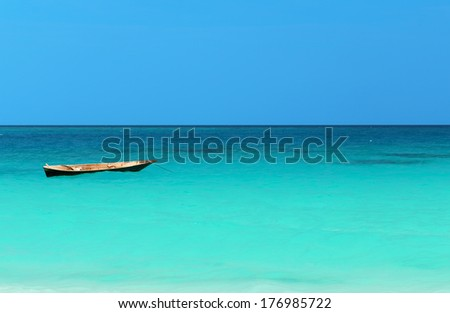 A Boat on the amazing turquoise water in the Indian ocean next to Mnemba atoll, Zanzibar, Tanzania - stock photo