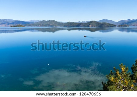 A boat on the deep blue mirror lake - stock photo