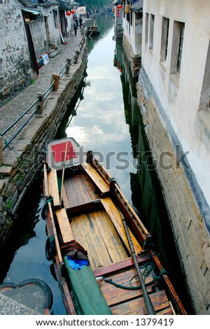 A boat on the narrow water river of a southern Chinese town. More with keyword Series11A. - stock photo