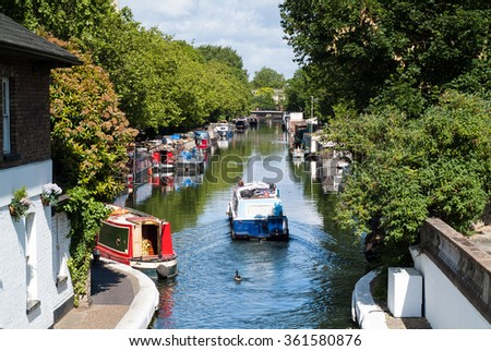 a boat travelling along the Little Venice canal in London on a sunny day - stock photo