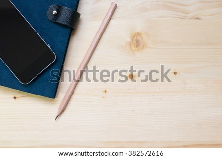 A book and smart phone on the desk