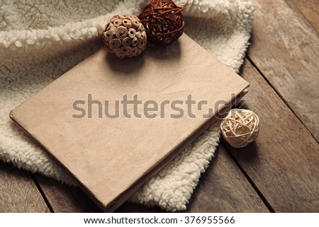 A book, decorative balls and a soft blanket on wooden background