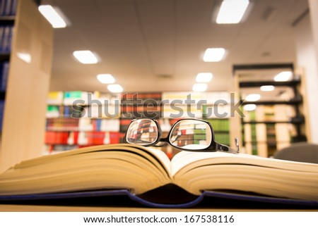 a book lying on the bookshelf with a glasses in Library  - stock photo