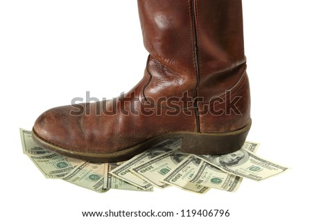 A boot stomps on money that is devalued and more worthless isolated on white