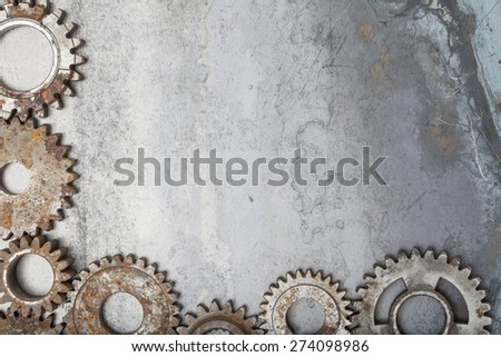 A border made up of interlocking rusty gears over a grungy steel background. - stock photo