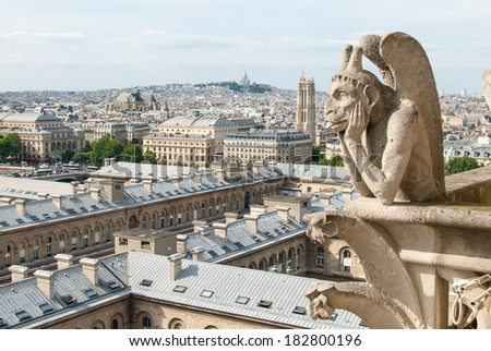 A bored gargoyle sits on top of Notre Dame surveying the Parisian cityscape below.
