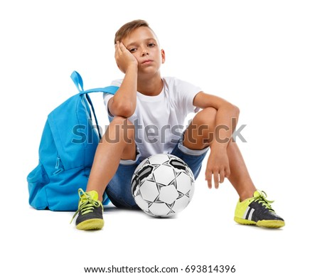 A bored kid with a bright satchel and a soccer ball isolated on a white background. A sitting child. Tired footballer kid. Copy space.