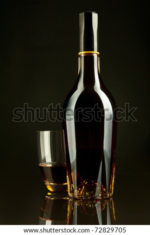 A bottle and a glass of cognac in a black background - stock photo