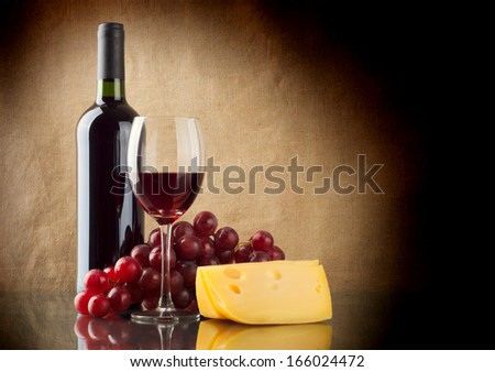 A bottle and a glass of red wine, a bunch of red grapes and cheese on linen background - stock photo