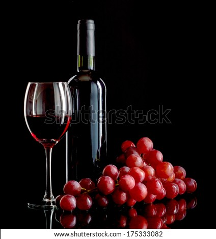 A bottle and a glass of red wine and a bunch of red grapes on black background