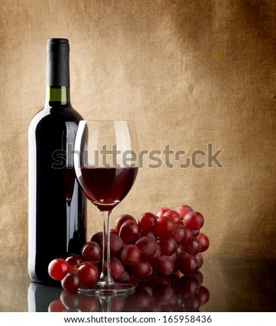 A bottle and a glass of red wine and a bunch of red grapes on linen background