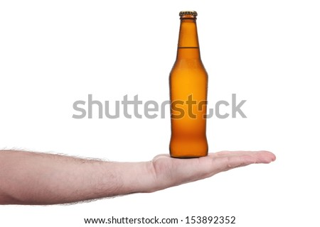 A bottle of beer in the palm of a hand.