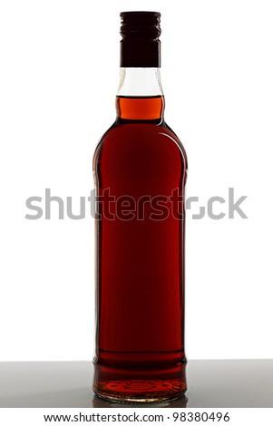 A bottle of brandy on a light background. - stock photo