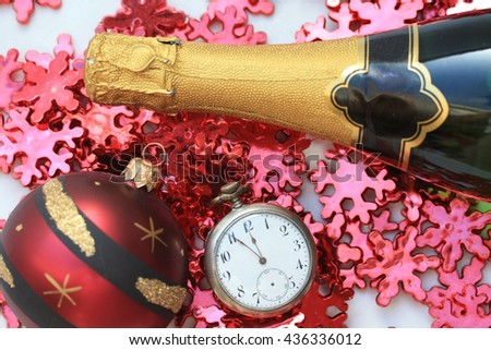 A bottle of champage with a pocket watch and red christmas decorations - stock photo