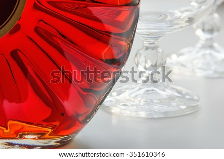 A bottle of cognac and empty glasses - stock photo