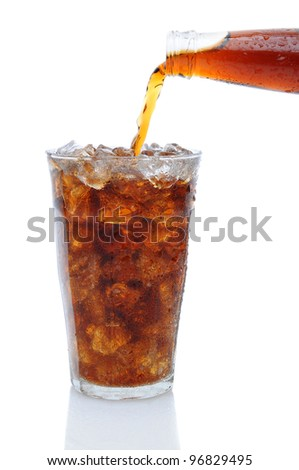 A Bottle of cola soda pouring into a glass filled with ice cubes over a white background with reflection. - stock photo