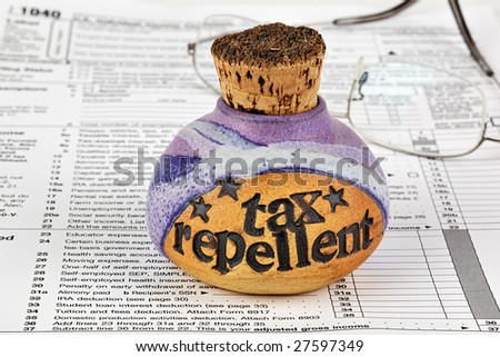 A bottle of corked tax repellent and eyeglasses on top of 1040 income tax form. - stock photo