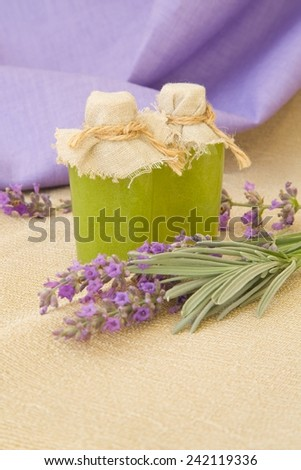 A bottle of lavender body scrub. Lavender twigs in the background. - stock photo