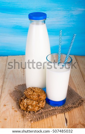A bottle of milk, a glass of milk with straws and cookies. On a blue background.