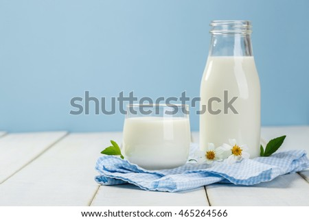 A bottle of milk and glass of milk on a white wooden table on a blue background, tasty, nutritious and healthy dairy products
