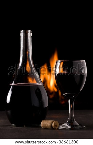 A bottle of red wine and a glass in front of a fireplace - stock photo