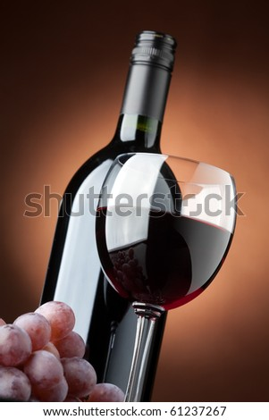 A bottle of red wine and a wine glass closeup - stock photo