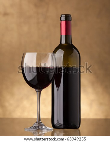 A bottle of red wine and filled with the same level of a wine glass on a golden background - stock photo