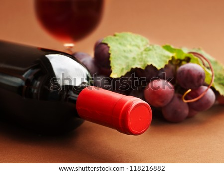 A bottle  of red wine, grapes and a glass - stock photo