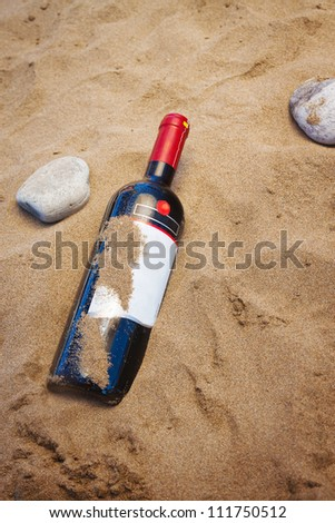 A bottle of red wine on the sand - stock photo
