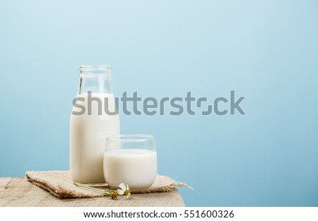 A bottle of rustic milk and glass of milk on a wooden table on a blue background, tasty, nutritious and healthy dairy products