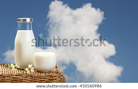 A bottle of rustic milk and glass of milk on wicker on a blue sky background, tasty, nutritious and healthy dairy products