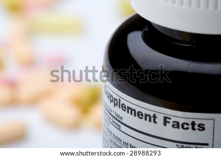 A bottle of vitamins (supplements) in foreground, and various supplements in the background. Selective focus. - stock photo