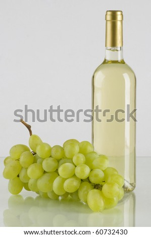 A bottle of white wine with grapes