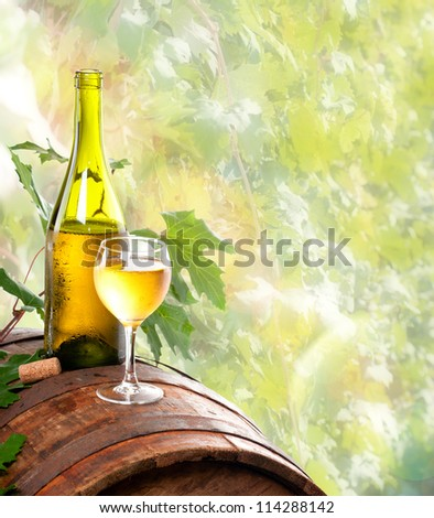 A bottle of wine and a glass of wine standing on an old wooden barrel. Against the background of the vine. - stock photo