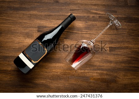 a bottle of wine and wine glass on old wood background. Food background - stock photo