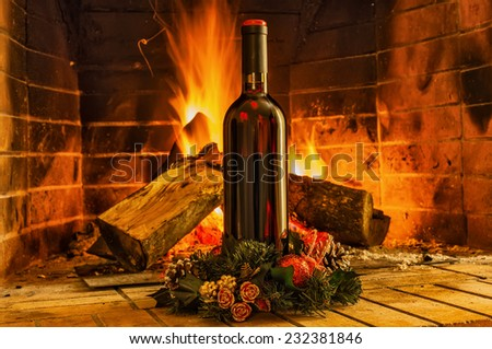A bottle of wine on the background of the fireplace and Christmas decoration - stock photo