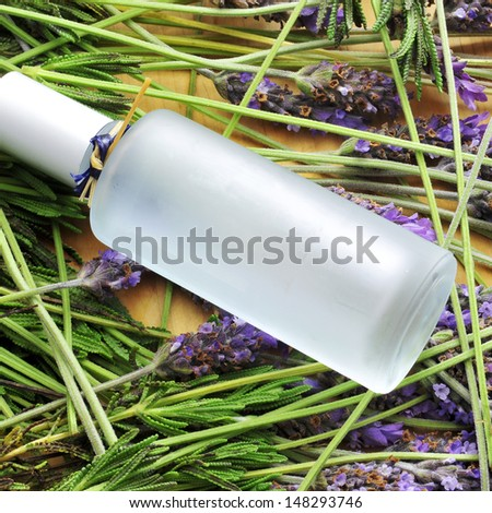 a bottle with fresh cologne and a pile of lavender flowers - stock photo
