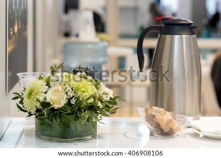 A bouquet of flowers and a pot of coffee on the table in the office - stock photo