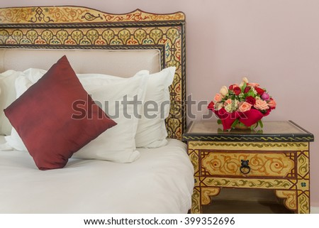 A bouquet of flowers on a bedside table next to a bed with a painted headboard - stock photo