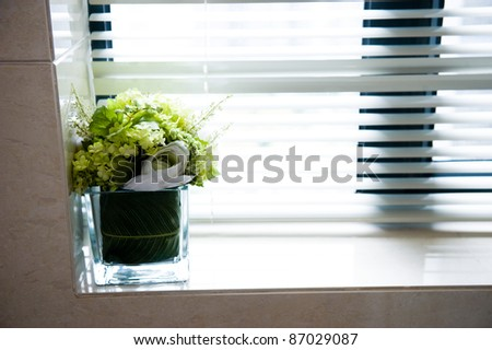 A bouquet of flowers standing on the window sill windows closed shutters. - stock photo
