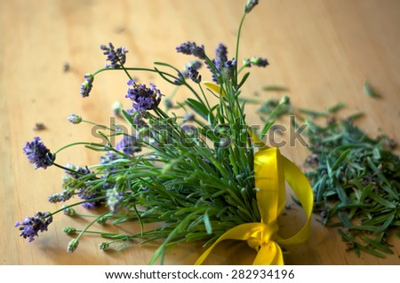 A bouquet of freshly cut lavender on wooden surface with yellow bow and extra leaves. - stock photo