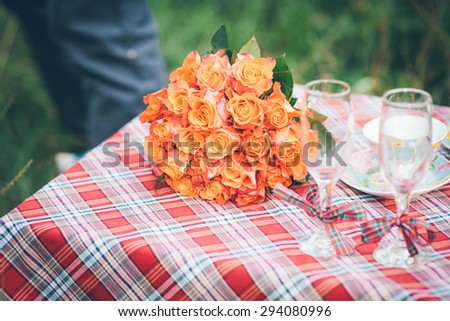 A bouquet of orange and pink flowers with two wine goblets lying on a wedding table - stock photo