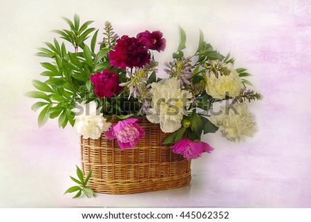 A bouquet of pink and white peonies in the basket . Still life with flowers.