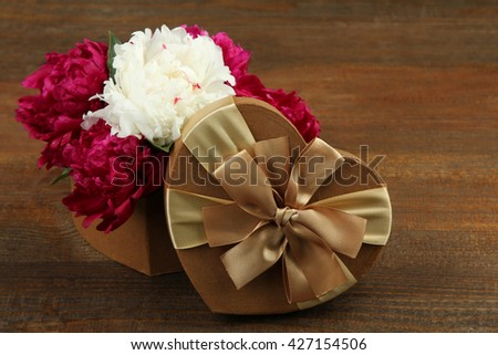 a bouquet of red and white peony on a wooden background near the boxes