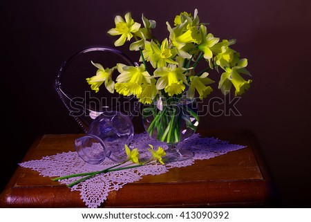 A bouquet of spring daffodils in water and a yellow veil on a brown background . - stock photo