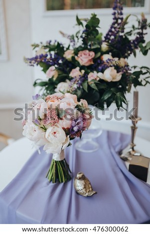 A bouquet of white and pink flowers and greenery is on the table in a wedding photo area