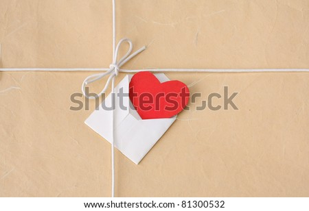 A bow from a string with valentine card on a brown packing paper - stock photo