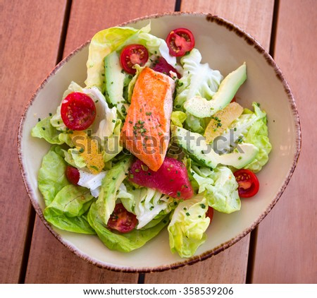 a bow of fresh salad with vegetables, salmon and grapefruit - stock photo