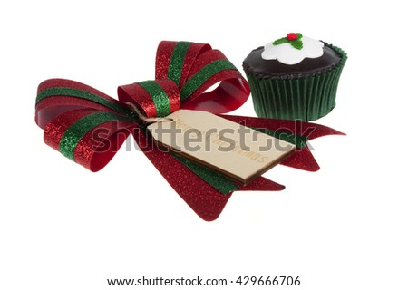 A Bow with a wooden Merry Christmas tag and a cupcake isolated on a white background - stock photo