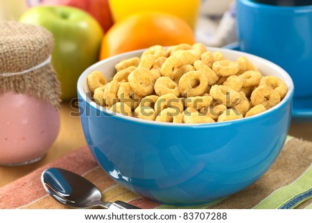 A bowl full of honey flavored cereal loops, yogurt in glass, fresh fruits, orange juice and coffee (Selective Focus, Focus on the cereal loop in the middle of the bowl) - stock photo